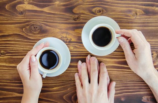 Tazze con un caffè nelle mani di uomini e donne.