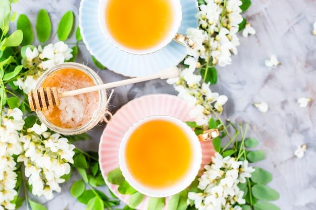 Tazze d'epoca con tè accanto a un barattolo di miele e acacia su un tavolo grigio