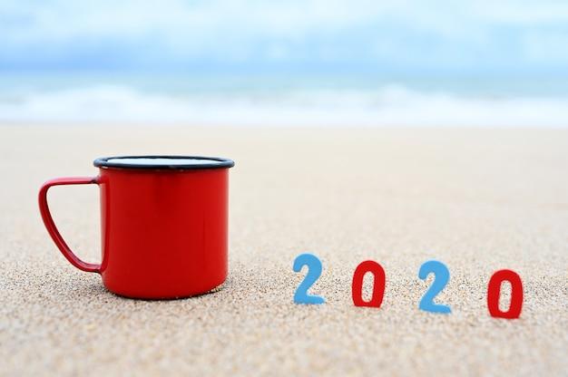Tazze da caffè e 2020 danno il benvenuto al nuovo anno sulla spiaggia del mattino.