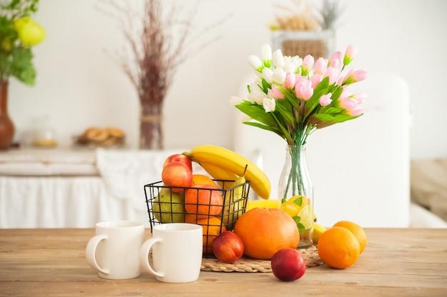 Tazze da colazione e frutta. tulipani di primavera sul tavolo.