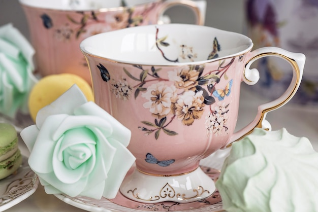 Tazze da tè rosa con ornamenti floreali e amaretti