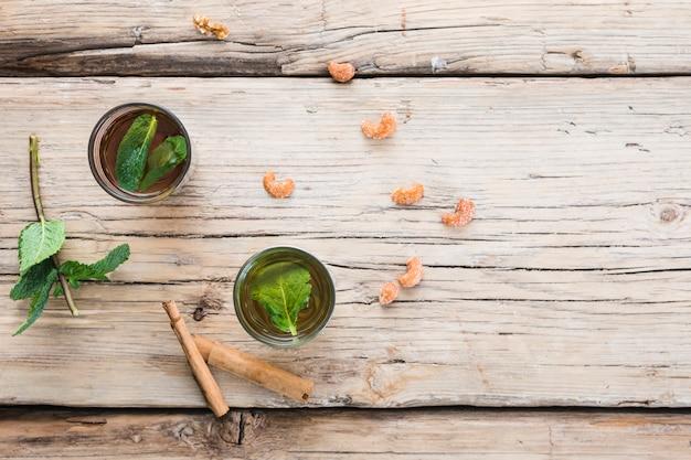 Tazze della bevanda vicino a cannella, piante e dadi a bordo