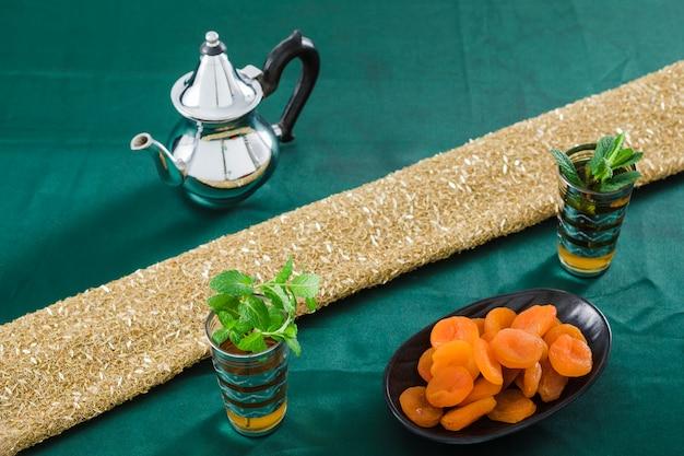 Tazze della bevanda vicino alla teiera e albicocche secche