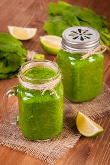 Tazze di barattolo di vetro riempite con spinaci verdi e frullato di cavolo verde