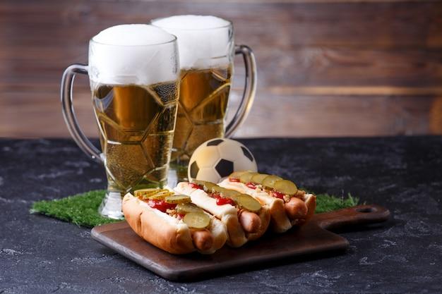 Tazze di birra con schiuma e hot dog su una tavola di legno