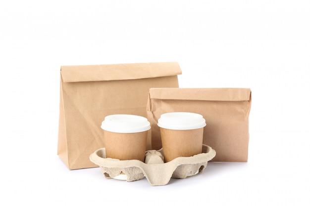 Tazze di caffè e sacchi di carta ecologici isolati su bianco