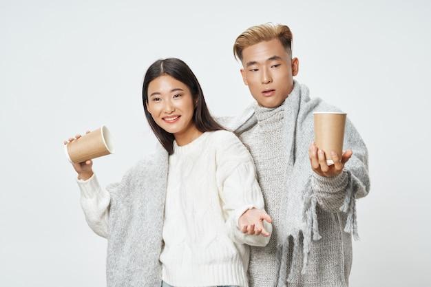 Tazze di caffè nelle mani di una giovane coppia di aspetto asiatico socializzante stile di vita grigio