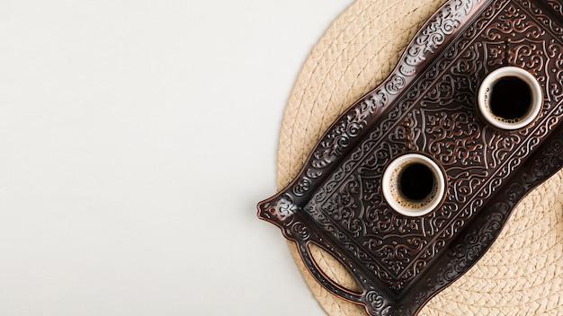 Tazze di caffè sul vassoio contro tappetino