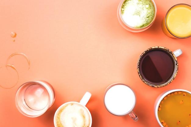 Tazze di caffè, tè, succo di frutta e acqua. bevande mattutine per diverse preferenze. vista dall'alto.