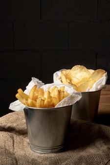 Tazze di metallo con patatine fritte e patatine fritte