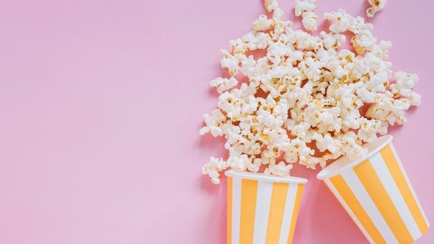 Tazze di popcorn su sfondo rosa