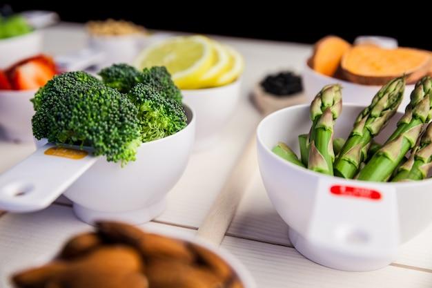 Tazze di porzione di ingredienti sani sul tavolo di legno
