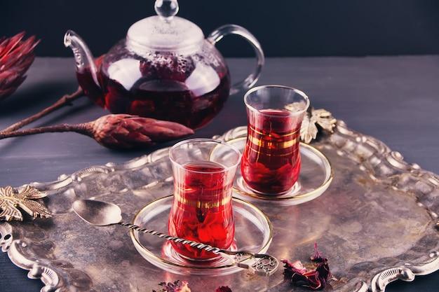Tazze di tè caldo karkade rosso con teiera sul vassoio