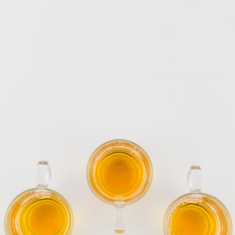 Tazze di tè di vetro di erbe verdi su fondo bianco
