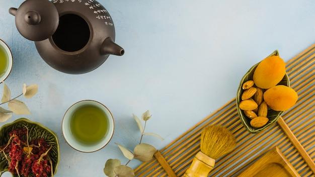 Tazze di tè tradizionali marroni con foglie e frutta secca su sfondo bianco
