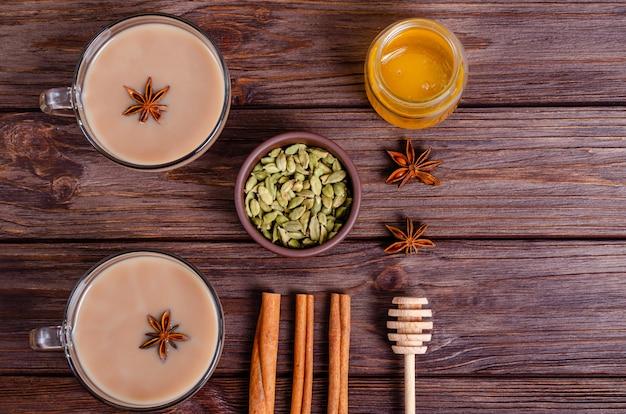 Tazze di vetro del tè indiano tradizionale di masi di chai su un vassoio con gli ingredienti