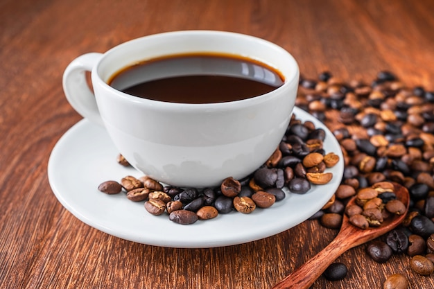 Tazze e chicchi di caffè di caffè su una tavola di legno