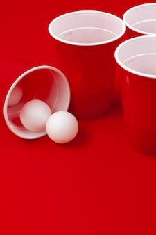 Tazze e palla di plastica su fondo rosso. gioco del beer pong