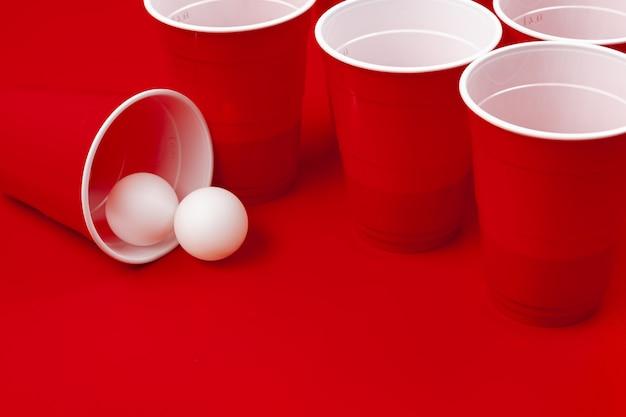 Tazze e palla di plastica su superficie rossa. gioco del beer pong