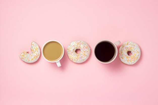 Tazze e tazza di carta con caffè o tè, ciambelle dolci gustose fresche esposte in linea su uno sfondo rosa. concetto di fast food, prodotti da forno, colazione, dolci, caffetteria. vista piana, vista dall'alto, copia spazio.