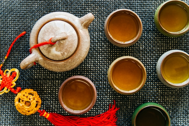 Tazze e teiera in ceramica con nappina su tovaglietta