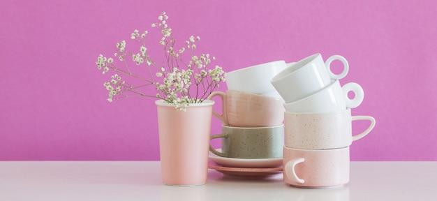 Tazze moderne sulla tavola bianca sulla parete di rosa del fondo
