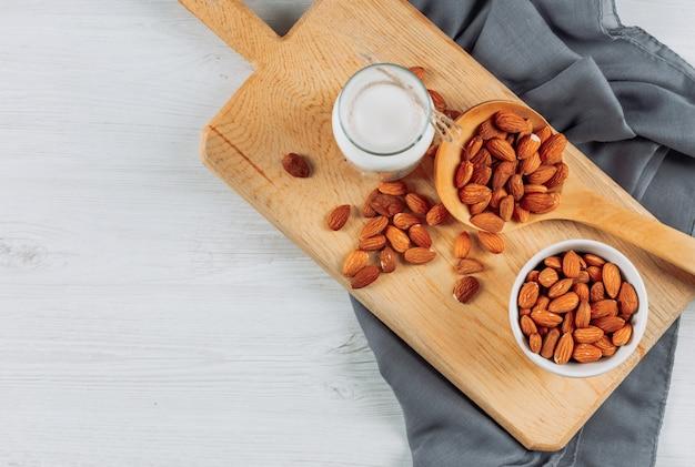 Tazze piatte di latte con nocciole, mandorle e noci diverse su fondo di legno bianco. orizzontale