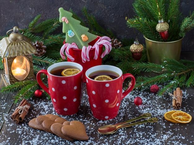Tazze rosse con tè, una canna di caramello, biscotti a forma di cuore, una lanterna con una candela