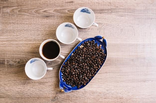 Tazze vicino a chicchi di caffè
