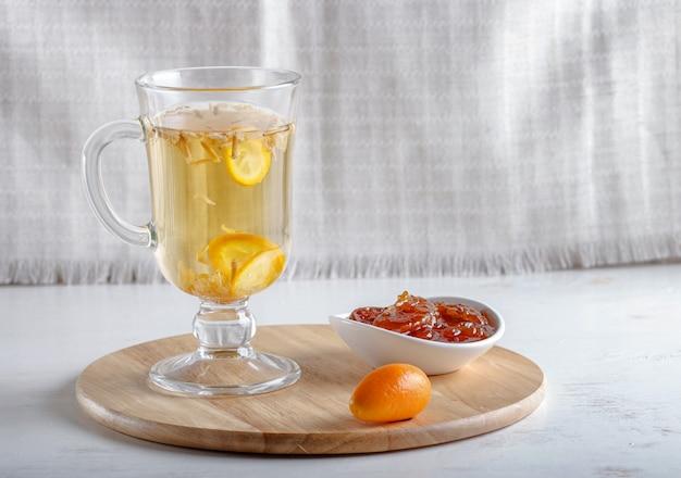 Tè al gelsomino con kumquat in una tazza di vetro su una tavola di legno su uno sfondo bianco