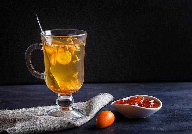 Tè al gelsomino con kumquat in una tazza di vetro su una tavola di legno su uno sfondo nero