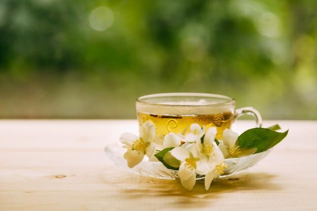 Tè al gelsomino in morbida luce calda della sera con fiori di gelsomino freschi