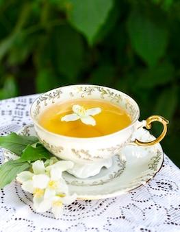 Tè al gelsomino in una tazza di porcellana e fiori di gelsomino su una tovaglia di pizzo