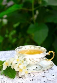 Tè al gelsomino in una tazza di porcellana e fiori di gelsomino