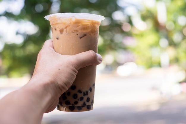Tè al latte ghiacciato con bubble boba in bicchiere di plastica in mano, bevanda fresca al tè di latte ghiacciato di taiwan