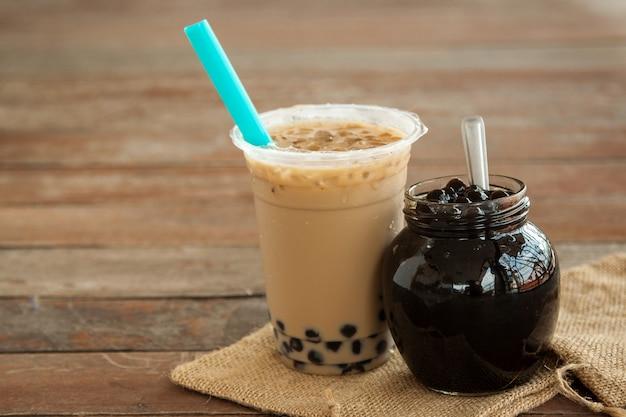 Tè al latte ghiacciato di taiwan e bubble boba nel bicchiere di plastica e boba nel barattolo di vetro
