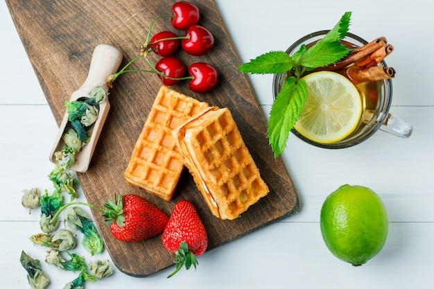 Tè al limone, cialda, erbe secche, frutta, menta, cannella in una tazza su legno e tagliere, piatto disteso.