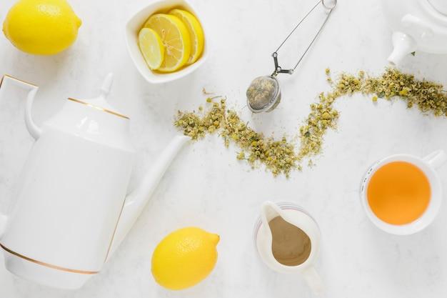Tè al limone con bollitore e foglie secche