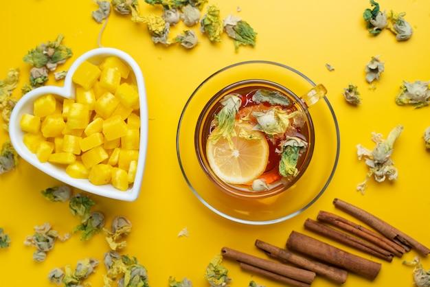 Tè al limone con erbe secche, zollette di zucchero, bastoncini di cannella in una tazza su superficie gialla, piatto disteso.