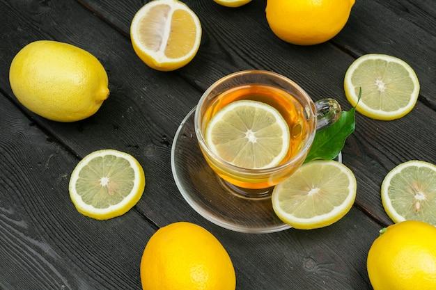 Tè al limone con limone e lime sul tavolo di legno