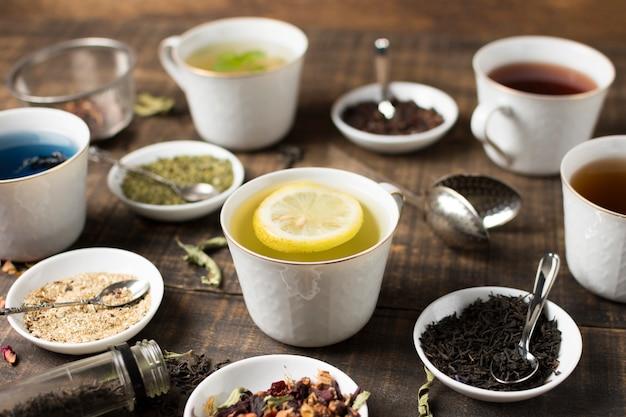 Tè al limone e diversi tipi di erbe sul tavolo di legno