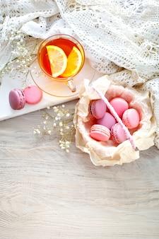Tè al limone, fiori selvatici e macaron sul tavolo di legno bianco