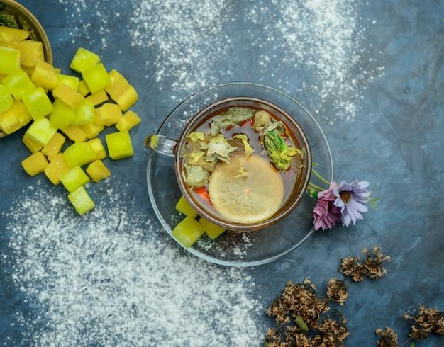 Tè al limone in una tazza con zollette di zucchero, vista dall'alto di erbe secche sulla superficie blu sgangherata