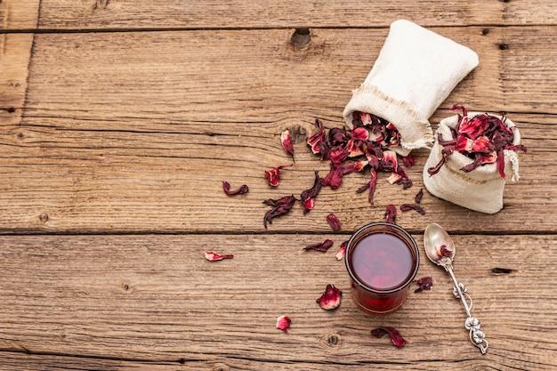 Tè all'ibisco caldo. petali secchi, sacchi di lino. cibo sano e concetto di cura di sé.
