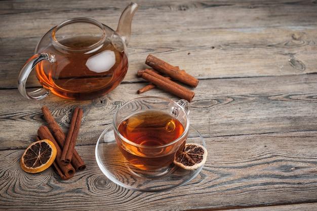 Tè alla cannella caldo aromatico sulla tavola di legno