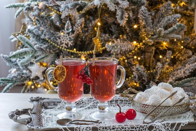 Tè alla frutta in tazze e meringhe con albero di natale