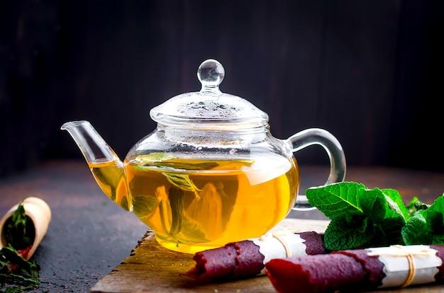 Tè alla menta caldo in una teiera e rotolo in pelle di frutta secca