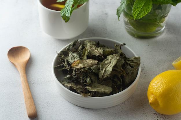 Tè alla menta, foglie di menta secca a prua, sulla superficie della luce, isolato,