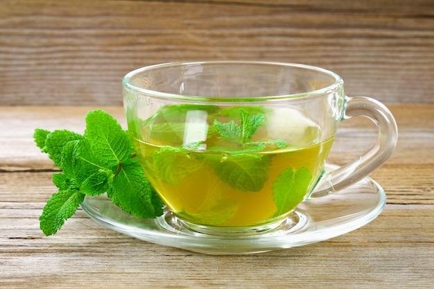 Tè alla menta organico fresco in vetro sulla tavola di legno.
