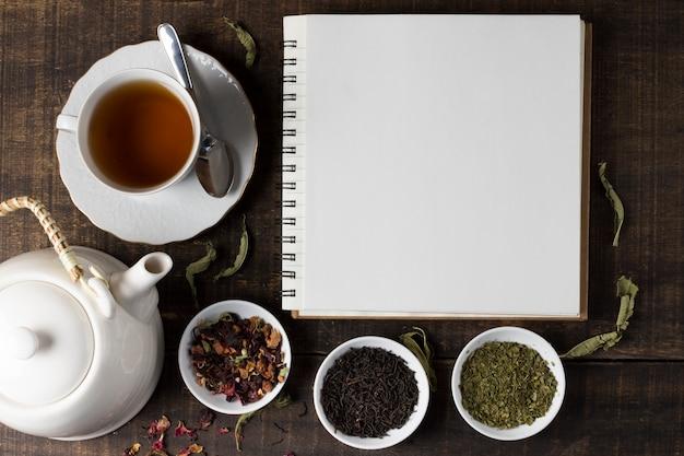 Tè alle erbe con la teiera e taccuino a spirale in bianco sulla tavola di legno